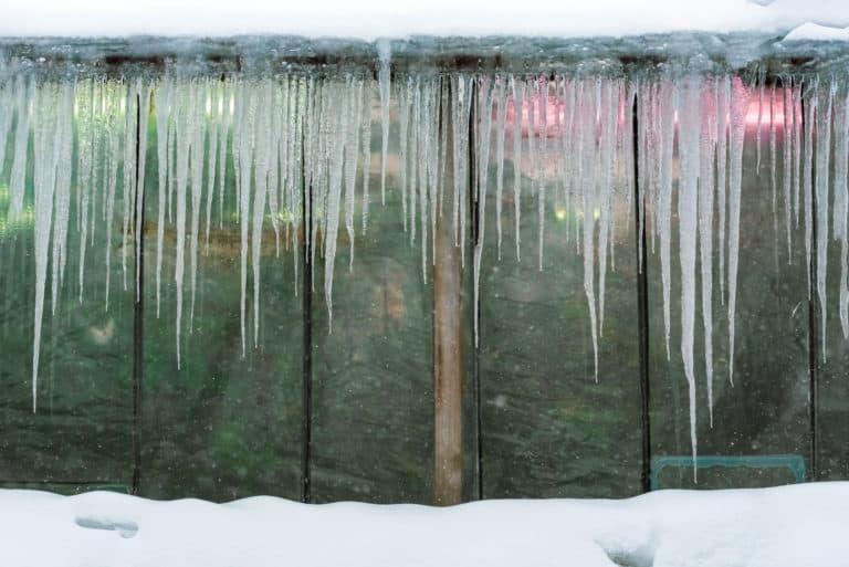 Eiszapfen-bedeckten bewölkten Gewächshaus Fenster, Winter Hintergrund